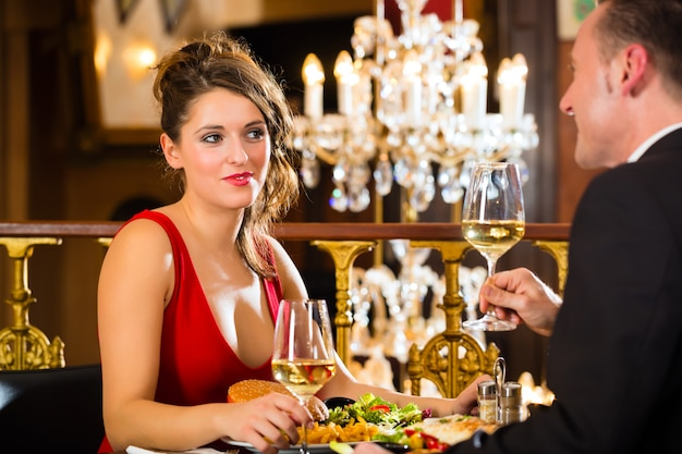 Happy couple have a romantic date fine dining restaurant, a large chandelier