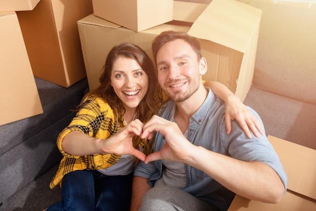 幸せなカップルは、すべてのパッケージを移動して配置する必要があります。成功、変化、積極性、そして未来のコンセプト