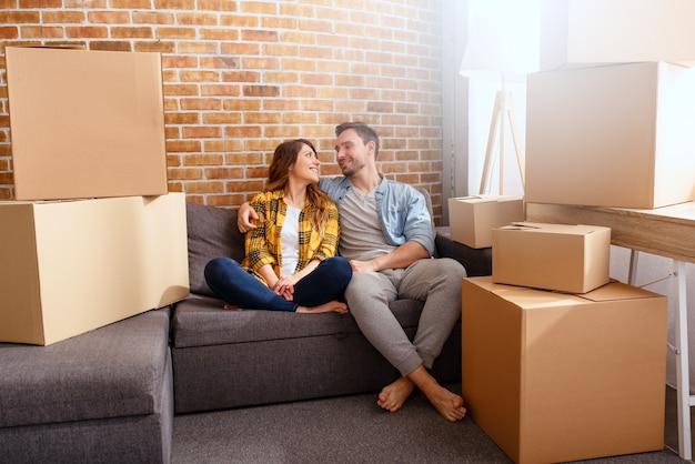 행복한 커플은 모든 패키지를 새 집으로 옮기고 정리해야합니다.