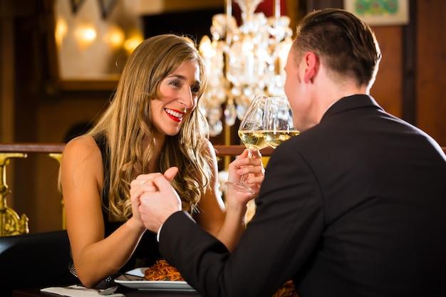 高級レストランでロマンチックなデートを持っている幸せなカップル