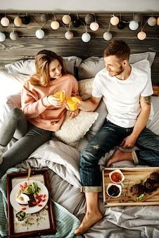 ベッドで朝食をとっている幸せなカップル