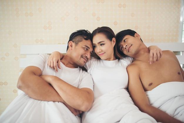 침실에 복잡한 관계와 사랑의 삼각형을 갖는 행복한 커플