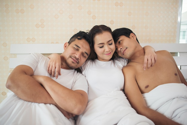 Happy couple having complicated affair and love triangle in bedroom