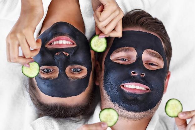 Happy couple having facial in spa salon