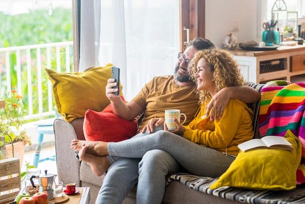 ソファに座って携帯電話で自分撮りをしながら楽しんで抱きしめる幸せなカップル。家でコーヒーを飲みながら一緒に余暇を過ごす幸せな白人カップル。