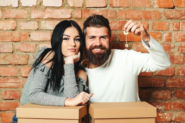 Счастливая пара весело и катается в картонных коробках в новом доме