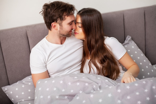 Happy couple having fun in bed. intimate sensual young couple in bedroom enjoying each other.