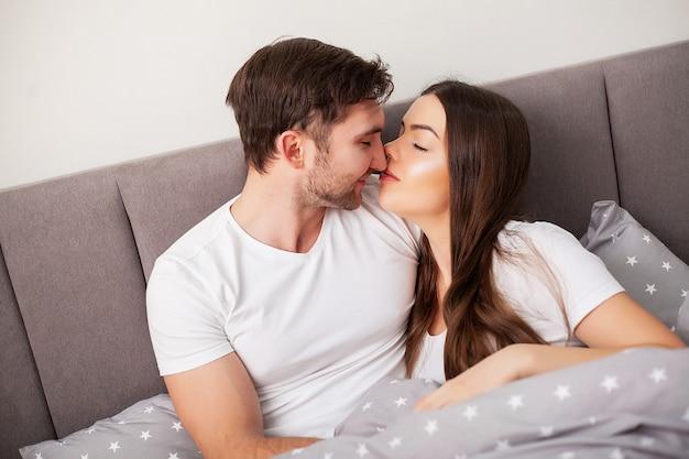 침대에서 재미 행복 한 커플입니다. 서로 즐기고 침실에서 친밀한 관능적 인 젊은 부부