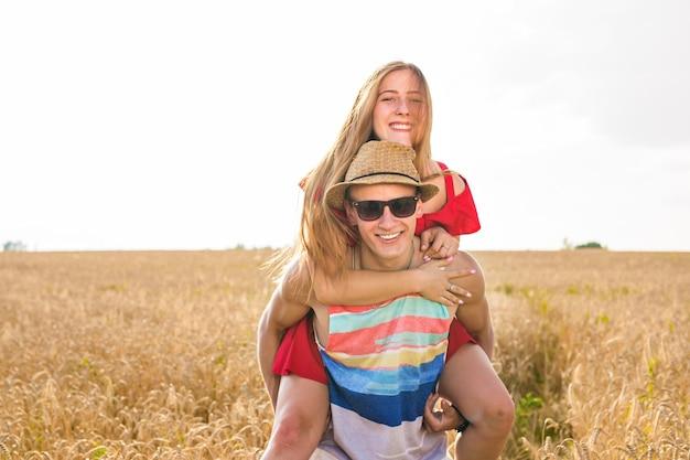일몰 동안 밀밭에서 야외에서 즐거운 시간을 보내는 행복한 커플. 함께 웃는 즐거운 가족. 자유 개념입니다. 피기백