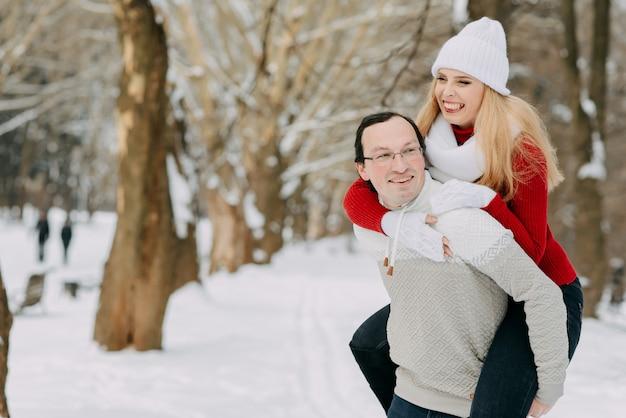 Happy couple having fun outdoors in snow park.