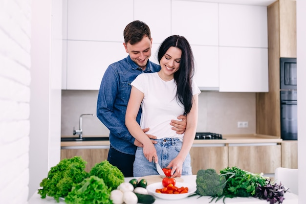 サラダを準備して自宅のキッチンに立って楽しんで幸せなカップル
