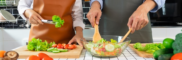 Happy couple having fun standing in kitchen at home preparing vegetable salad