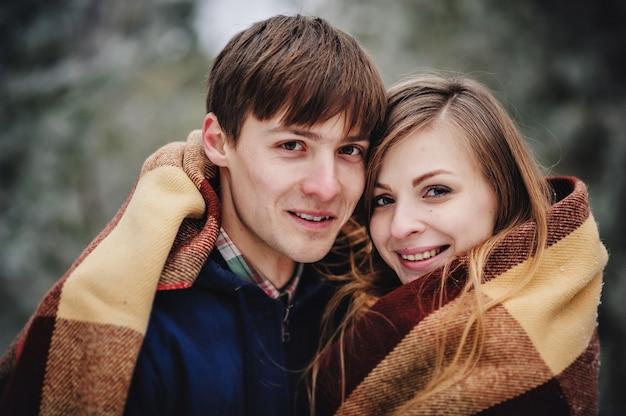 雪の公園で屋外で楽しい時間を過ごしている幸せなカップル。男と女は毛布を持って歩きます。冬休み。