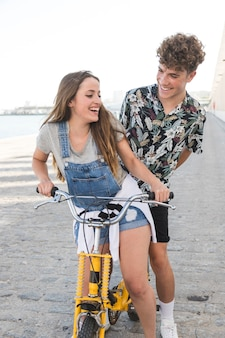Happy couple having fun together while riding bicycle