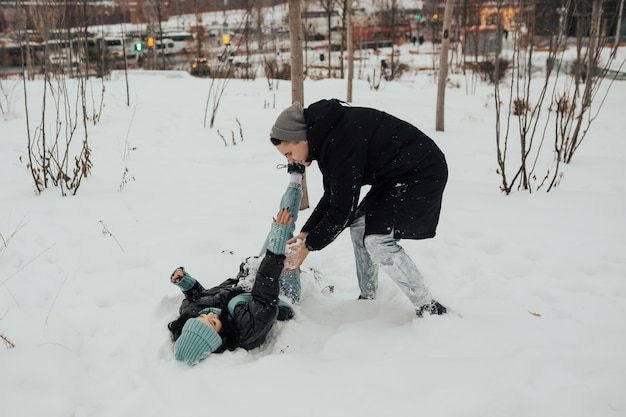 都市公園でスノーボールファイトをしながら楽しんで幸せなカップル