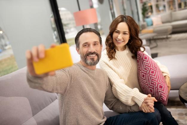 自撮りを作る家具サロンで楽しい時間を過ごしている幸せなカップル