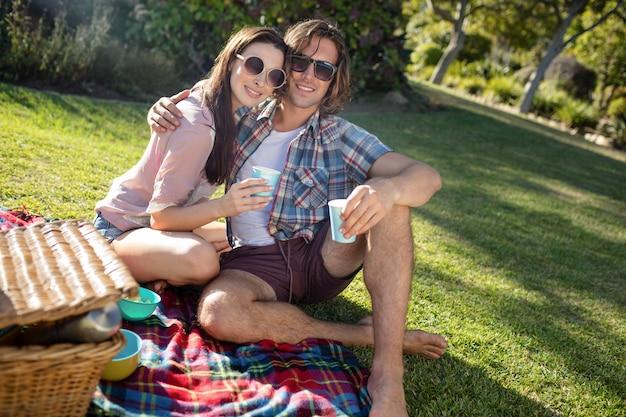 公園でピクニックを持っている幸せなカップル