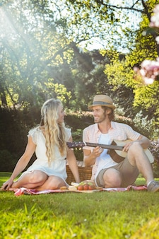 Happy couple having a picnic and playing guitar in the garden