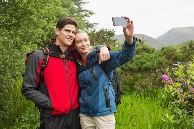 Happy couple on hike taking a selfie