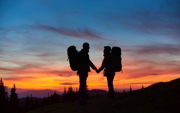 Happy couple hiking together holding hands standing with their backpacks on top of a mountain during stunning sunset