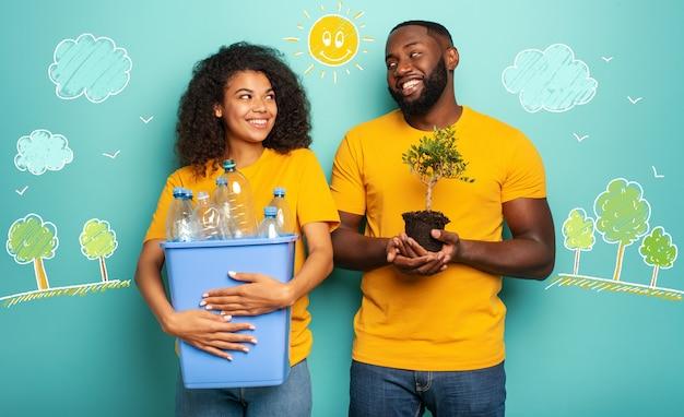 행복한 커플은 생태 보존 재활용 및 지속 가능성의 밝은 파란색 개념 위에 병 플라스틱 용기와 작은 나무를 보유