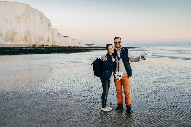 幸せなカップルがカメラドローン空気quadrocopterを保持、海辺で時間を過ごす