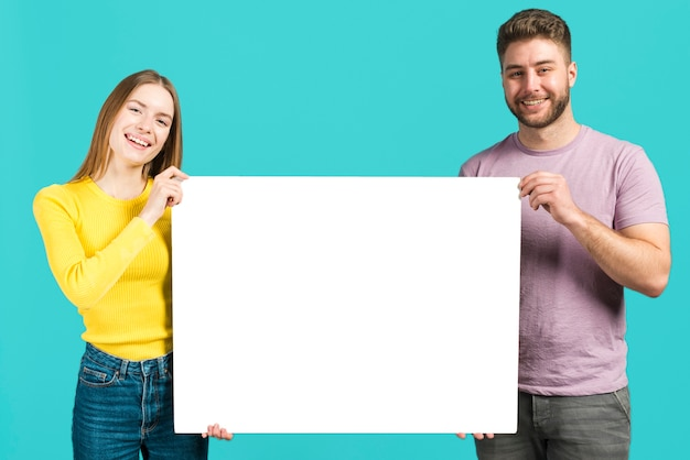 Happy couple holding blank sign