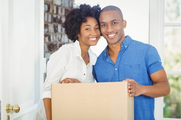 Happy couple holding box out of their house