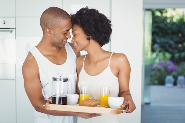 Happy couple holding breakfast tray in the kitchen at home