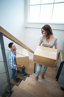 Happy couple holding cardboard boxes while climbing steps