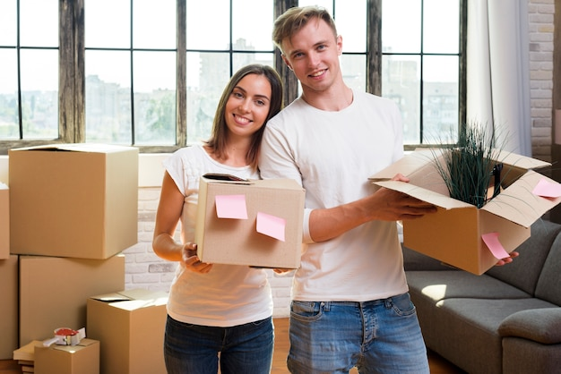 Happy couple holding cardboard boxes