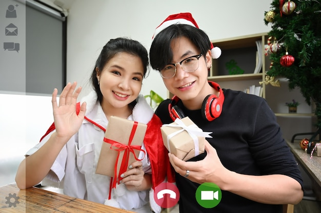 Happy couple holding christmas gift and having video call.
