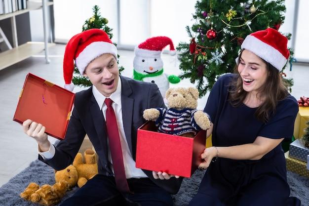 テディベアで贈り物を交換し、クリスマスにプレゼントを贈る幸せなカップル