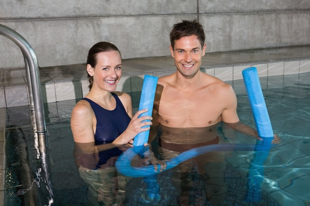 Happy couple holding foam rollers smiling at camera