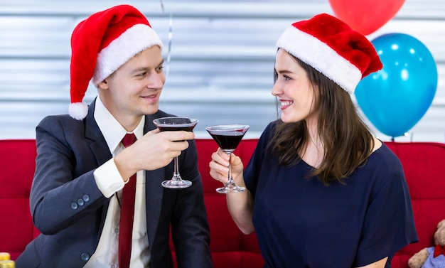 Happy couple holding glasses with santa hats