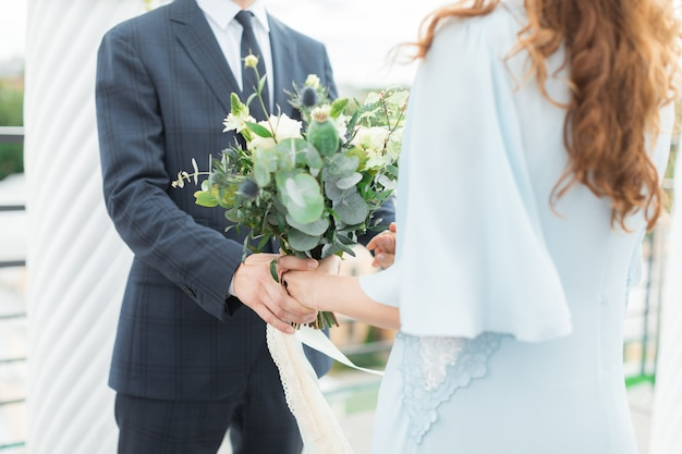 Happy couple holding hands in the aisle of a luxurious wedding arch
