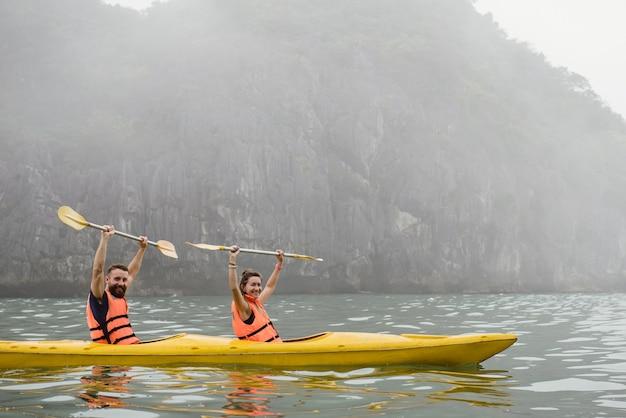 Halong bay의 안개 낀 바다에서 손과 카약 노를 머리 위로 잡고 있는 행복한 커플. 스포츠 개념의 승리와 성공.