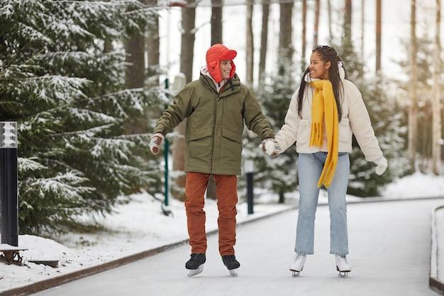 公園でスケートをしながら手をつないで、お互いに笑顔の幸せなカップル