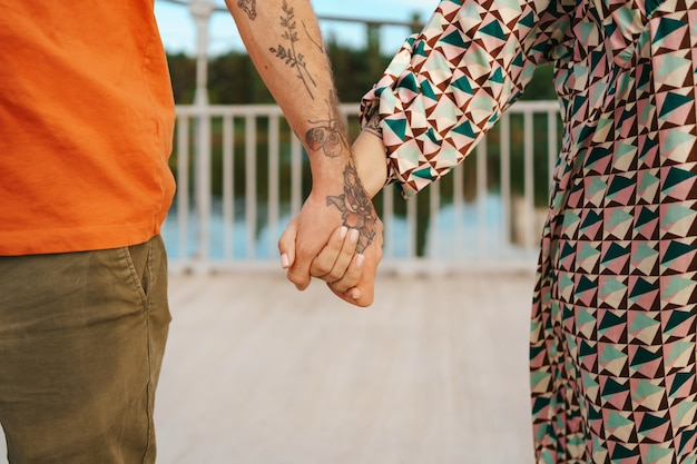 Happy couple holding hands in colorful clothes close up