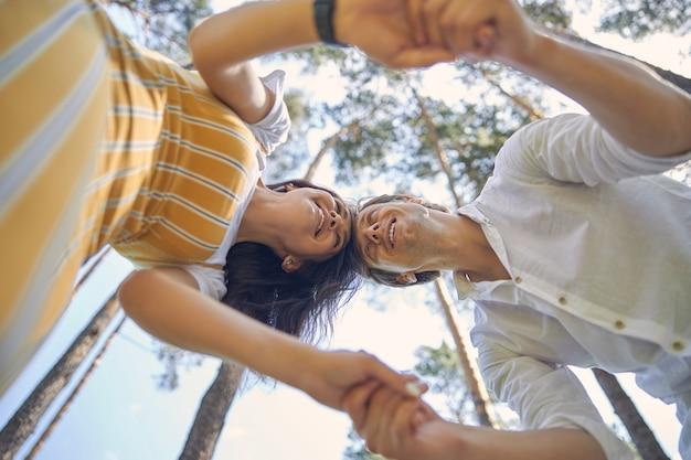 좋은 따뜻한 날씨를 즐기면서 숲에서 함께 손을 잡고 행복한 커플