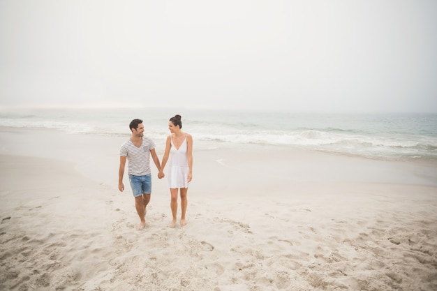 Happy couple holding hands and walking on the beach