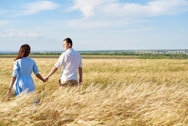 Счастливая пара, взявшись за руки, гуляет по лугу. понятие любви, хороших отношений, взаимопонимания и гармонии.
