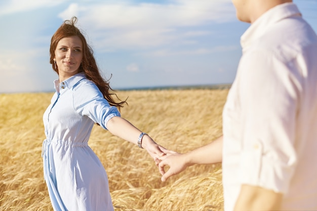 Happy couple holding hands walking through a meadow. the concept of love, good relationships