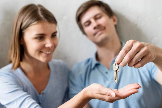 Happy couple holding keys to old property