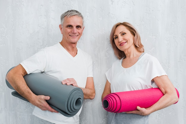 Happy couple holding leaning white wall holding rolled yoga mat