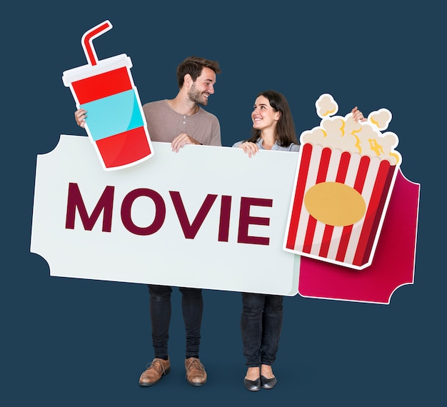 Happy couple holding movie icons