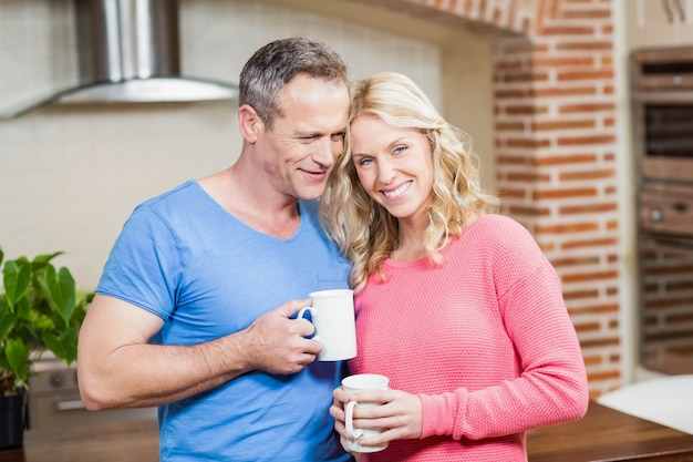 Happy couple holding mugs in the kitchen