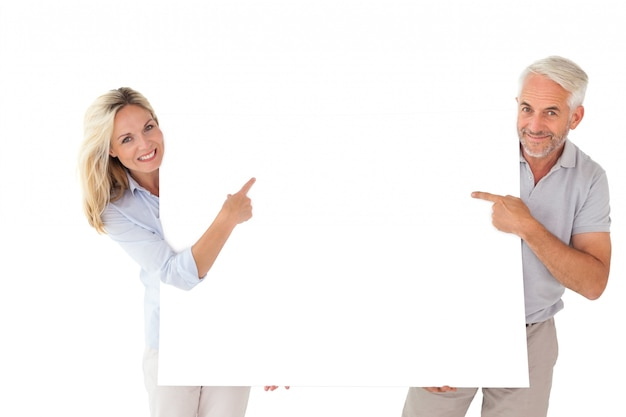 Happy couple holding and pointing to large poster