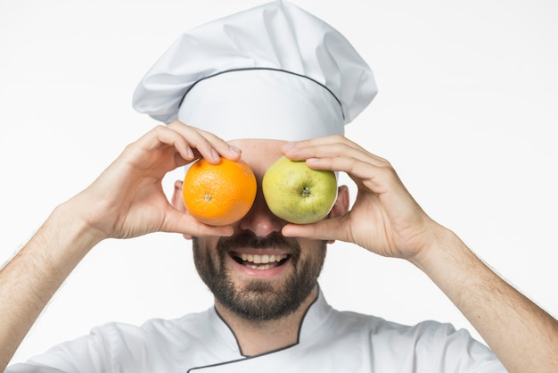 Happy couple holding ripe fruits in front of his eye against white background
