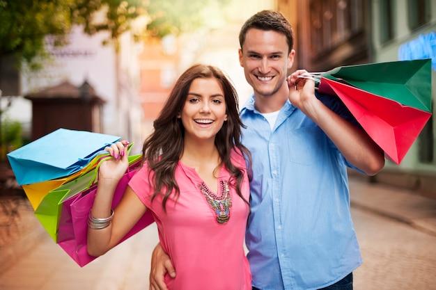 Счастливая пара, держащая хозяйственную сумку
